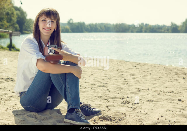 Young smiling woman resting at the beach with old camera. Hipster girl posing near water. Warm color toned image - Stock-Bilder