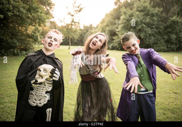 Three children dressed in costume for Halloween Night. - Stock-Bilder