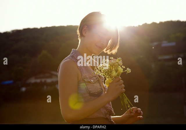Young woman in meadow holding bunch of wild flowers - Stock Image