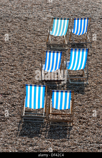 Brighton, East Sussex, England, UK. Deckchairs on the pebble beach - Stock Image