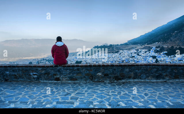 Tourist observing a panoramic view of blue city of Chefchaouen at rising, Morocco - Stock Image