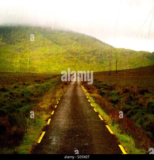 A road with no cars on it leading into the mountains. Co Kerry, Ireland - Stock-Bilder
