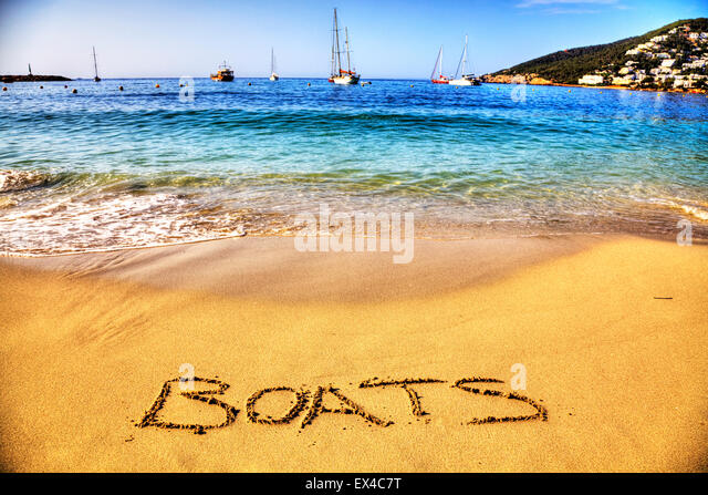 boats boat boating word in sand written on beach fun resort seas coast coastline holidays vacations trips trip getaway - Stock Image