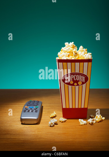 Popcorn in container and Remote Control on table - Stock Image
