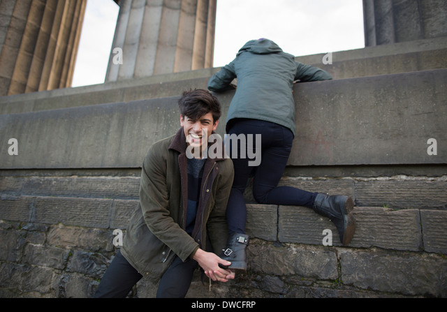 A young man helps his girlfriend climb onto the National Monument on Calton Hill in Edinburgh, Scotland - Stock Image