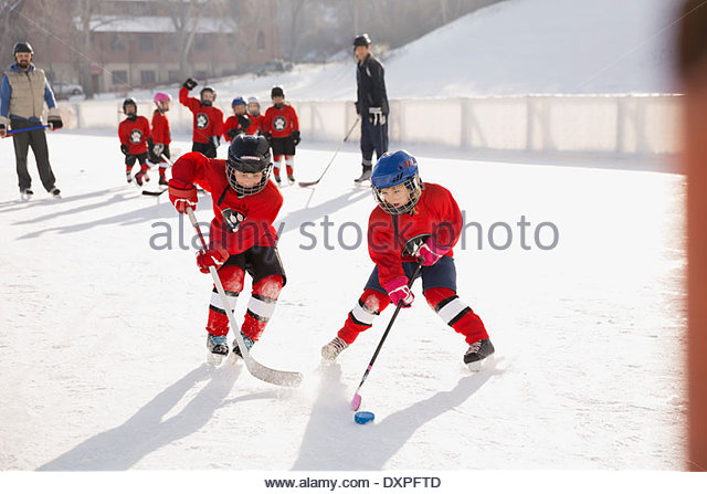Young hockey players practicing on ice rink - Stock Image