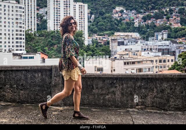 Fashion model walking and smiling at camera - Stock Image