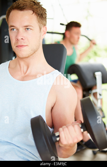 Two Young Men Training In Gym With Weights - Stock-Bilder