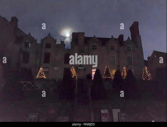 a view of Hay-on Wye Castle at dusk with the moon behind it and Christmas lights on it's ornamental trees - Stock Image