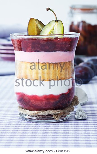 A layered dessert consisting of plum compote, sponge cake and quark served in a glass - Stock Image