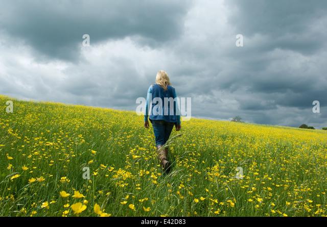 Woman walking in field of buttercups - Stock Image