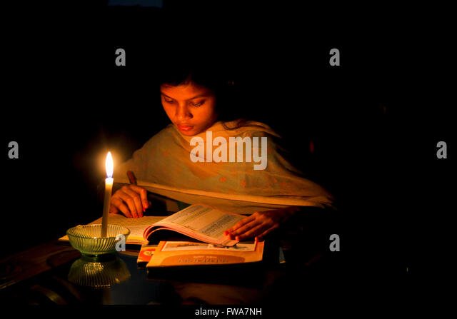A Bangladeshi young kid she reads from the school book on candle lights in Dhaka, Bangladesh. © Jahangir Alam - Stock-Bilder