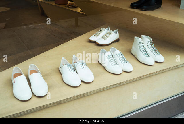 Five different styles of men's white leisure shoes for summer on display in the window of a New York City boutique - Stock-Bilder