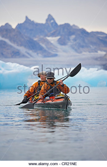 Men rowing canoe on still glacial sea - Stock Image