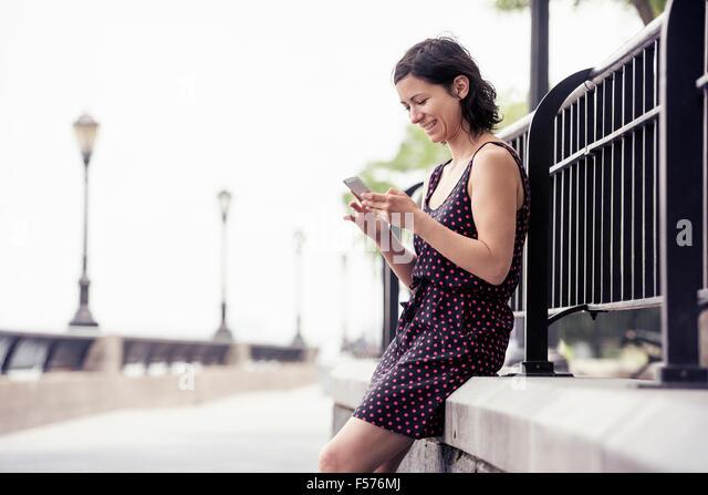 A woman pausing on a street, sitting and checking her cell phone. - Stock Image