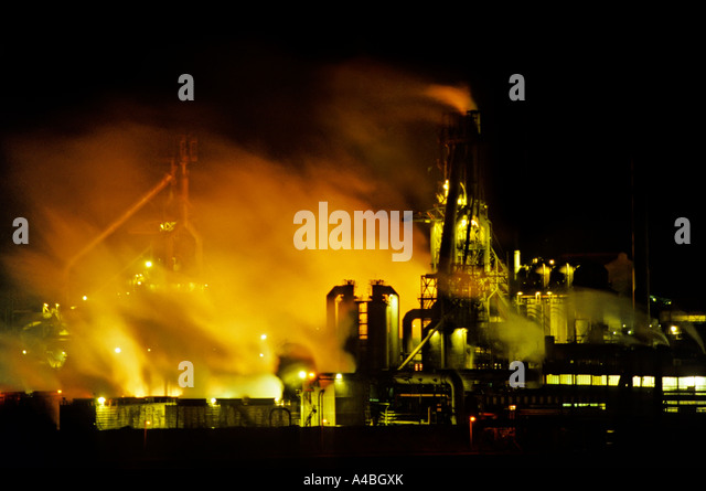 Smoke and fumes rising from floodlit steelworks Port Talbot Wales UK - Stock Image