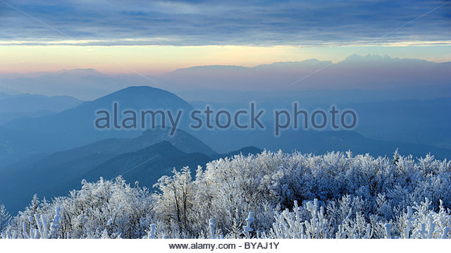 Beautiful winter landscape at sunset with fog and snow - Stock Image