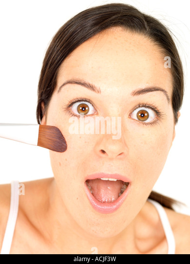 Shocked Young Woman Applying Blusher Model Released - Stock Image