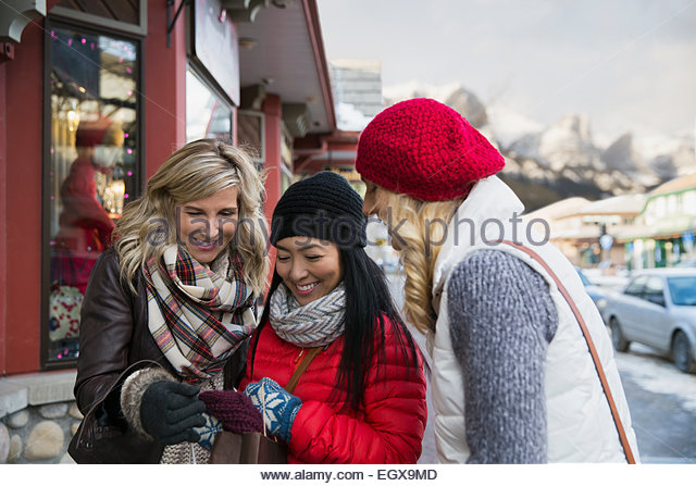Women in warm clothing looking at scarf - Stock Image