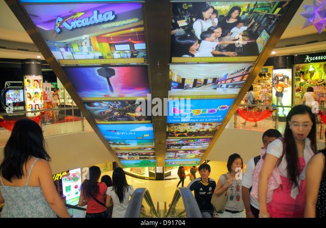Singapore Bugis Junction shopping advertising escalator Asian man woman - Stock Image