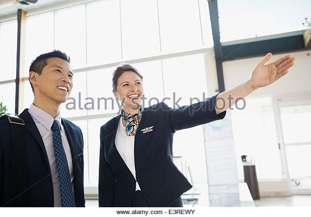 Airport customer service representative guiding businessman - Stock Image