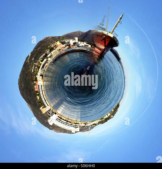 Big red freighter on a quay in Bergen harbour, Norway. Turned into a tiny planet / world. - Stock Image
