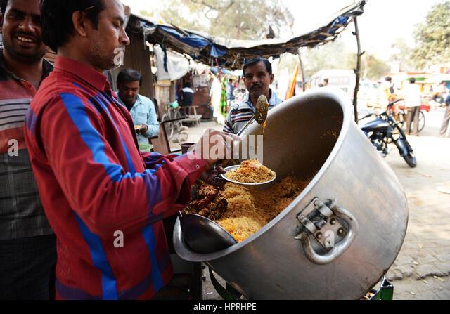 A Biryani vendor serving Chicken Biryani from his pot in Kannauj, Uttar Pradesh, India. - Stock Image