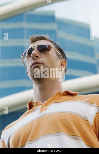 A young man in casual dress wearing sunglasses stands in front of a modern high rise building - Stock Image