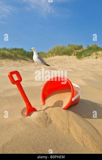 A concept image of a 'bucket and spade' beach holiday with a seagull in the background. - Stock-Bilder