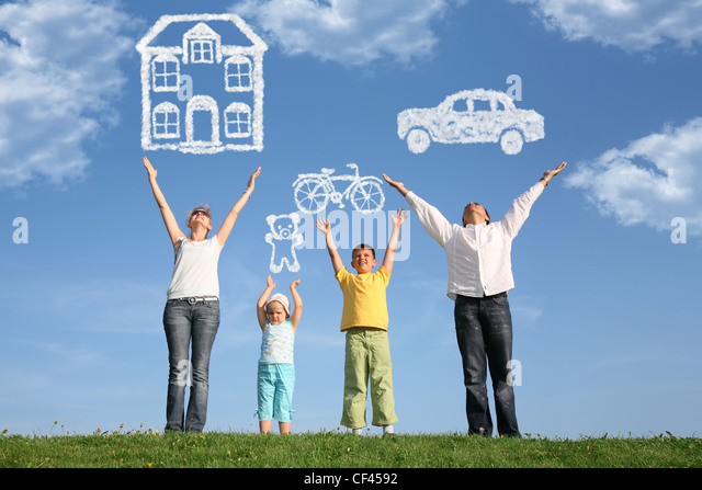 family of four on grass with hands up and dream - Stock-Bilder