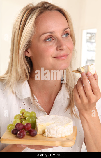 WOMAN EATING CHEESE - Stock Image