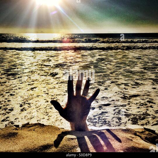 Help! Hand Reaching Up From The Water Into The Light - Stock Image