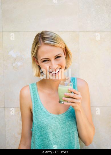 Smiling woman drinking detox - Stock Image