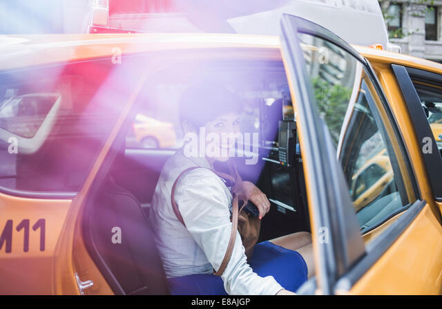 Woman getting into yellow taxi, New York, US - Stock Image