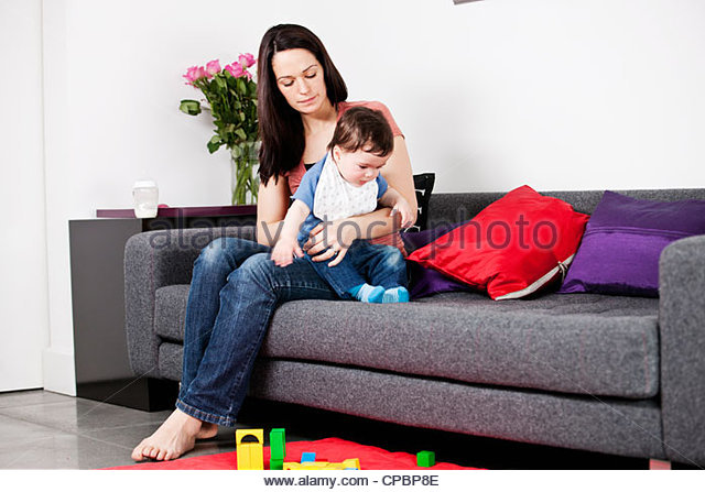 A mother sitting on a sofa winding her baby - Stock-Bilder
