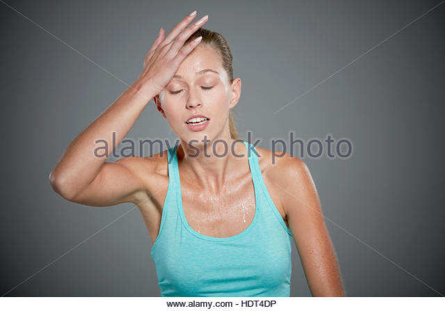 Portrait of sweating young woman with her hand on her head. - Stock-Bilder