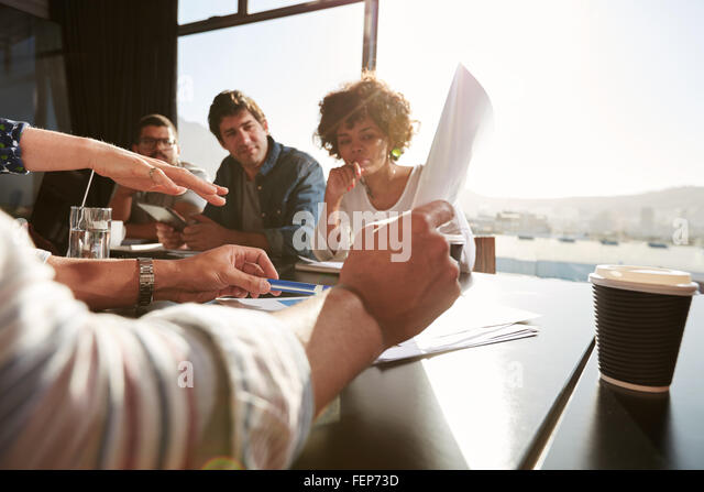 Hands of young man and woman explaining business plan to colleagues, Creative team having a meeting in office. Focus - Stock Image