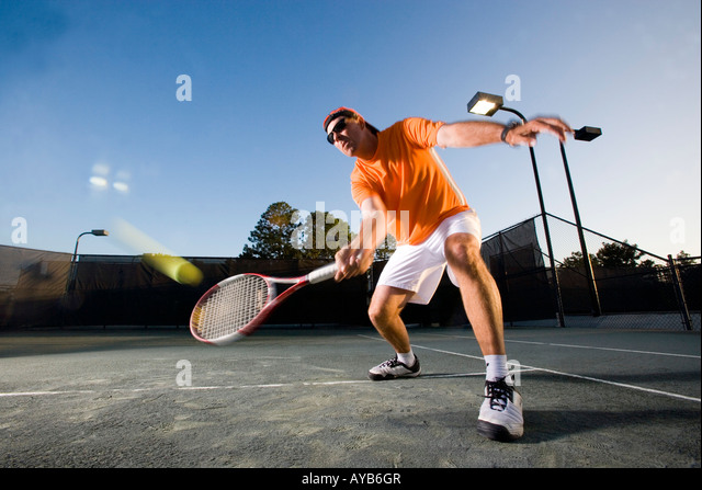 Tennis player hitting a volley at the service line - Stock Image