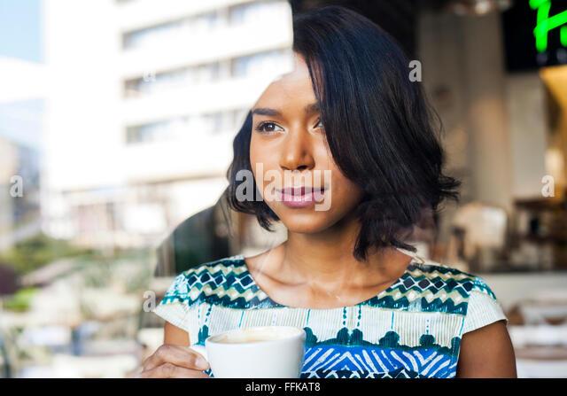 Mixed race woman takes a coffee break - Stock Image