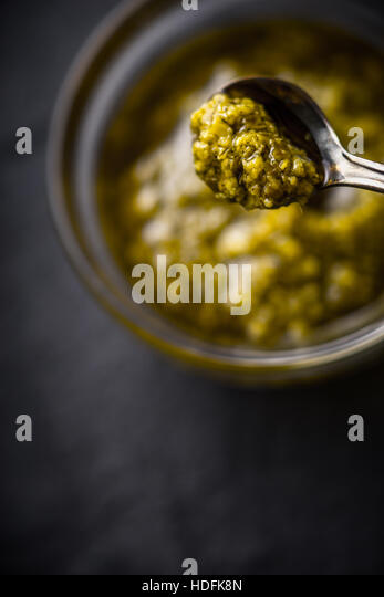 Pesto sauce in the metal spoon with blurred jar vertical - Stock Image