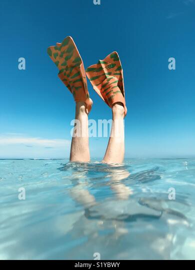 A female with colored fins on diving into the water. Natadola Beach, Fiji - Stock Image