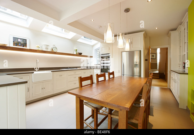 Kitchen side extension London terrace Oak table skylights Velux feature green wall - Stock Image