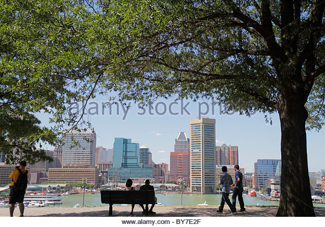 Baltimore Maryland Federal Hill Park Inner Harbor Patapsco River port waterfront skyline tree park bench view shade - Stock Image