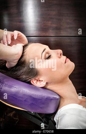 Female masseur massaging young woman's head in beauty salon - Stock-Bilder