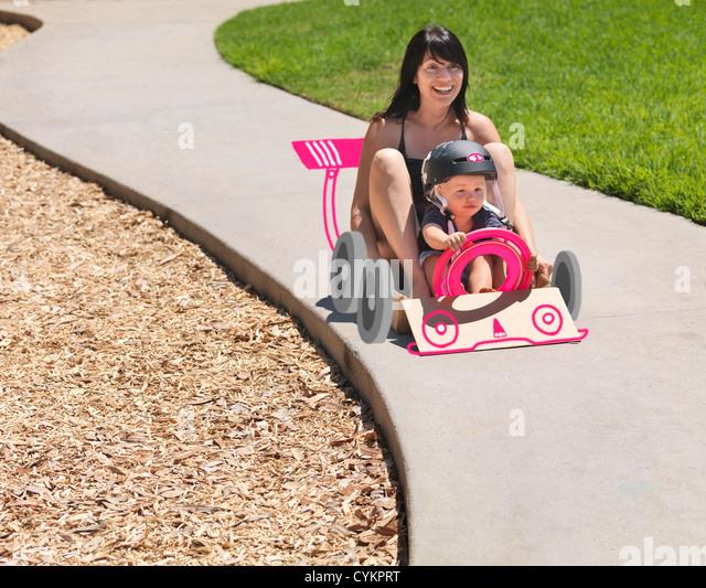 Mother and son driving go kart - Stock-Bilder