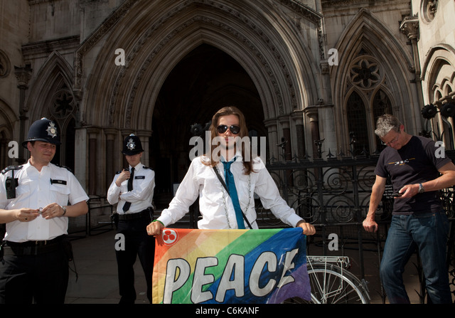 Josh, a resident of Democracy village, protests for peace outside the Royal Courts of Justice during the hearing. - Stock Image