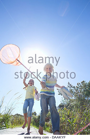 Enthusiastic boy and girl holding fishing nets - Stock Image