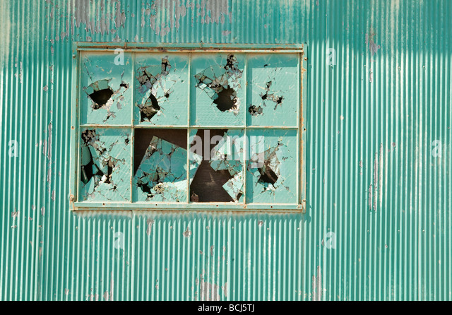 Green corrugated metal wall with broken glass windows - Stock Image