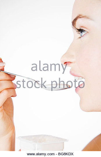 A Young Woman Eating A Yogurt - Stock Image