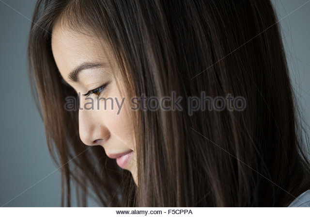 Close up profile pensive brunette woman looking down - Stock Image
